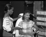 African American cosmetologist applying makeup to a customer, Los Angeles, 1984