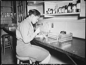 """Pfc. Johnnie Mae Welton, Negro WAC, laboratory technician trainee, conducts an experiment in the serology laboratory sf the Fort Jackson Station Hospital, Fort Jackson, SC."""