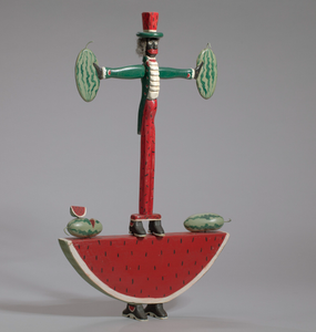 Sculpture in the form of a caricatured man standing on a watermelon slice