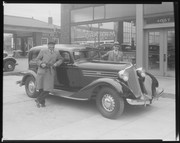 Jack Johnson and Mr. Mann posing next to a car in front of the Archer-Mann Motor Company, 4057 Lindell.