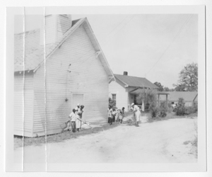 Photograph of African American men and women raking land in front of a wooden building, Clarkesville, Habersham County, Georgia, 1953