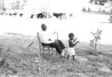 Elderly man and young boy in the yard of a house, observing a march in Prattville, Alabama, during a demonstration sponsored by the Autauga County Improvement Association.