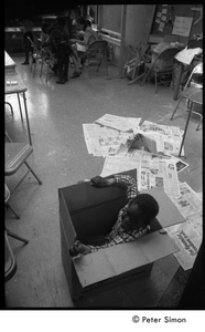 Young boy sitting in a cardboard box in the classroom, Liberation School