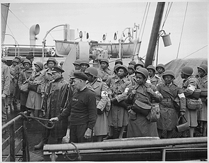 """U.S. Army nurses, newly arrived, line the rail of their vessel as it pulls into port of Greenock, Scotland, in European Theater of Operations. They wait to disembark as the gangplank is lowered to the dock."""