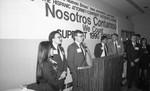 "ABA meeting participants standing near a ""Nosotros Contamos"" banner, Los Angeles,1990"