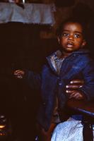 Child seated near a fireplace