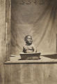African American infant in a washtub on a porch.