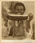 Smiling man eating watermelon, 1920