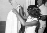 Susie Sanders in a bedroom in her home, putting on her gown before her graduation from Sidney Lanier High School in Montgomery, Alabama.