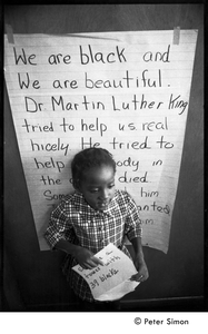 Young girl at the Liberation School, standing in front of a poster honoring Martin Luther King: 'We are black and beautiful. Dr. Martin Luther King tried to help us real nicely...'