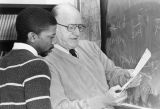 An Educational Opportunity Program student and a professor review an equation in front of a blackboard, 1984