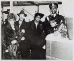 African American Captain Godfrey standing with four relatives of John H. Murphy, Sr. (from left to right: Mr. and Mrs. George B. Murphy, Sr., son and daughter-in-law; Mrs. John Murphy; and Miss Frances Murphy, daughter) at the launching of the Liberty ship bearing his name. Bethlehem-Fairfield Shipyard