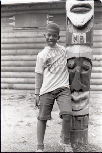 """African American boy in Spirit in Flesh t-shirt, posed next to """"totem pole"""" at summer camp"""