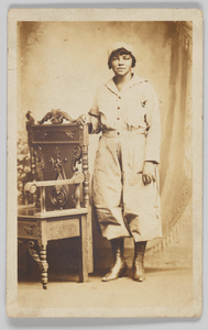 Photographic postcard of a woman standing next to a wooden chair