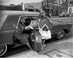 Women exit motor vehicle, Los Angeles, 1963