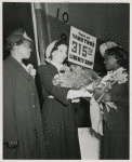 Miss Lulu Mae Hamel (flower girl and shipyard worker) presenting a bouquet of roses to Mrs. John H. Sengstacke (sponsor) during the launching of the Liberty ship SS Robert S. Abbott at Permanente Metals Corporation Shipyard No. 2