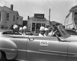 Women wearing Menelik fez caps riding in convertible past Famous Coffee Shop