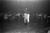 Two male dancers performing on the floor in front of the stage at the Laicos Club in Montgomery, Alabama, during a performance by Bobby Moore and the Rhythm Aces.