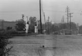 Two women walking across railroad tracks on a dirt road toward downtown Montgomery, Alabama.