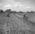 Two men on tractors, preparing a field for planting in Autauga County, Alabama.