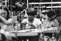 Women operate sewing machines in a garment shop