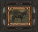 [Unidentified soldier in Union first lieutenant's uniform and kepi with cavalry saber atop horse in front of fence, building, and woods]