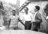 Stokely Carmichael, Rap Brown, and another young man standing beside a car after Carmichael's release from prison in Prattville, Alabama.