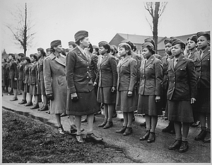 """Somewhere in England, Maj. Charity E. Adams,...and Capt. Abbie N. Campbell,...inspect the first contingent of Negro members of the Women's Army Corps assigned to overseas service."""