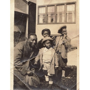 A man poses with three boys.