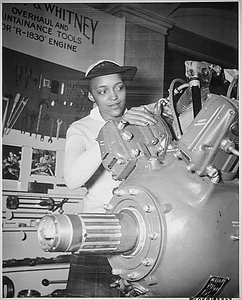 """""""Inspecting a Grumman Wildcat engine on display at the U.S. Naval Training School (WR) Bronx, NY, where she is a `boot' is WAVE Apprentice Seaman Frances Bates."""""""