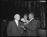 Archie Moore tests the biceps of Casey Stengel