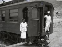 Waiter and chef at rear of T. & G. R. R. [Tonopah and Goldfield Railroad] car Louise at Tonopah, 1906.