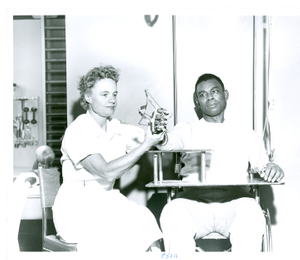 Photograph of a female physical therapist adjusting the hand splint of an African American patient at the Georgia Warm Springs Foundation, Warm Springs, Meriwether County, Georgia, 1959