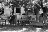 "African American man and white woman seated in the yard in front of a cinder block house, observing the ""March Against Fear"" through Mississippi, begun by James Meredith."
