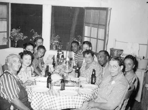 40 Club seated at table in a residence.