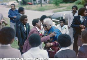 Photograph of young boy giving an elder woman a hug Conference on Black Women in the Arts