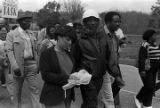 Dick Gregory and other marchers during the 20th anniversary reenactment of the Selma to Montgomery March, probably in rural Dallas or Lowndes County, Alabama.