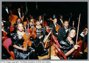 Photograph of a group of string musicians sitting in folding chairs Christmas/Kwanzaa Concert Hallelujah Hip Hop Concert, December 1995