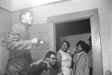 Group of young men and women talking, probably in an apartment.