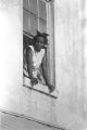 """Woman leaning out the second-story window of a building, observing the """"March Against Fear"""" through Mississippi, begun by James Meredith."""