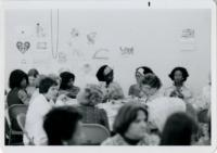Women Seated at a Table in a Large Group Setting