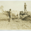 Booker T. Washington with student on ox cart