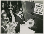Mrs. John H. Sengstacke, sponsor of the Liberty ship SS Robert S. Abbott, christens the ship by breaking a bottle of champagne against its hull on the day of its launching, Permanente Metals Corporation Shipyard No. 2