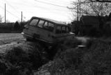 Car stuck in a ditch on the side of a dirt road, probably in Newtown, a neighborhood in Montgomery, Alabama.