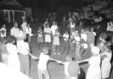Adults and children holding hands while standing in a circle on an unpaved street in a neighborhood in Montgomery, Alabama, during a civil rights demonstration.