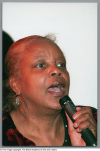 Woman speaking into microphone at Christmas Kwanzaa soiree Christmas/Kwanzaa Soiree