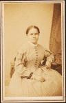 Studio portrait of unidentified seated woman wearing check dress