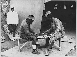[African American] soldiers in France engaged in a game of checkers in front of a Young Men's Christ...