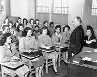 Principal Mortimer C. Ritter addresses an academic class at the Needle Trades High School, New York, in April 6, 1944. Students include Fergel Levine, Jean Cultrera, and Ellen Perino