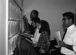 California Chicano News Media Association members examining postings, Los Angeles, 1994